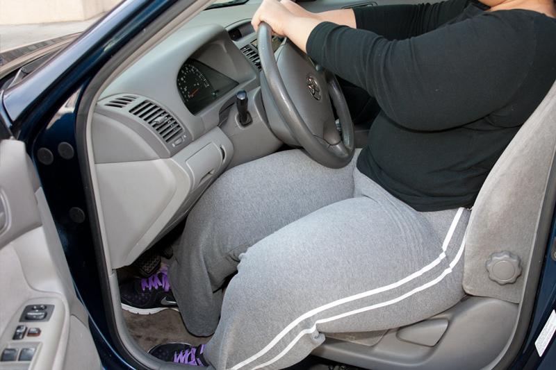 Una persona obesa con dificultad para salir de un automóvil compacto.